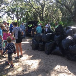 Volunteers collecting trash in wooded area image